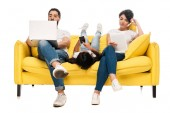 kid lying on sofa and holding smartphone with blank screen near latin parents using gadgets isolated on white