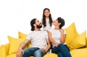 smiling latin parents sitting on sofa and looking at cute daughter isolated on white