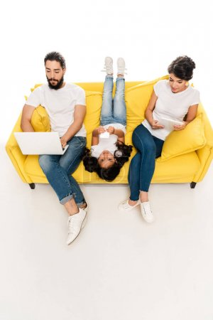Photo for Overhead view of kid lying on sofa and holding smartphone near latin parents using gadgets isolated on white - Royalty Free Image