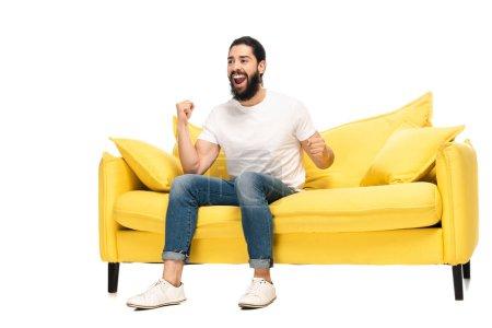 Photo pour Homme latin barbu observant le championnat tout en s'asseyant sur le sofa et célébrant le triomphe isolé sur le blanc - image libre de droit