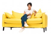 low angle view of upset latin woman sitting on sofa and looking at smartphone isolated on white