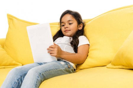 low angle view of latin kid using digital tablet while sitting on sofa isolated on white