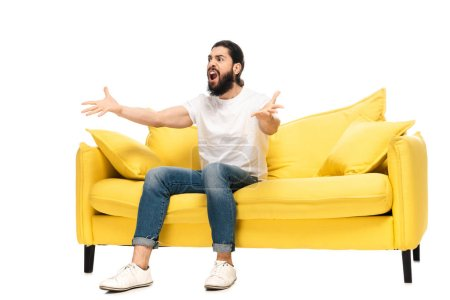 Photo for Bearded latin man watching championship while sitting on sofa and gesturing isolated on white - Royalty Free Image