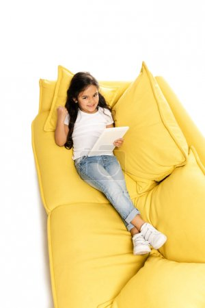 Photo for Overhead view of happy latin kid using digital tablet while lying on sofa and gesturing isolated on white - Royalty Free Image