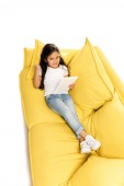 overhead view of happy latin kid using digital tablet while lying on sofa and gesturing isolated on white