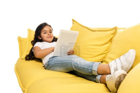 Photo for Selective focus of happy latin kid using digital tablet while lying on sofa isolated on white - Royalty Free Image
