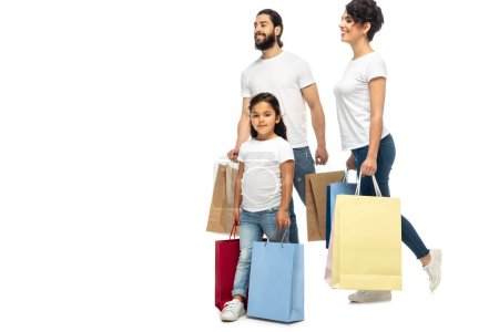 Photo for Happy latin parents holding shopping bags while standing with kid isolated on white - Royalty Free Image