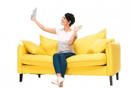 Foto de Mujer latina alegre sosteniendo tableta digital y agitando la mano mientras tiene videollamada aislada en blanco - Imagen libre de derechos