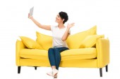 cheerful latin woman holding digital tablet and waving hand while having video call isolated on white