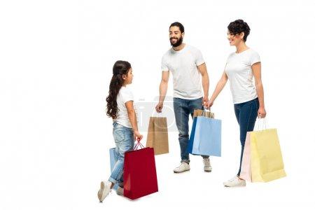 Foto de Padres latinos felices sosteniendo bolsas de compras mientras miran a la hija aislada en blanco - Imagen libre de derechos