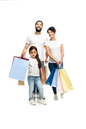 Photo for Happy latin parents holding shopping bags while standing with cute daughter isolated on white - Royalty Free Image