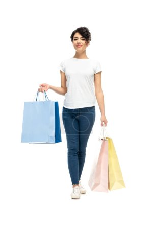 Photo for Happy latin woman standing with shopping bags and smiling isolated on white - Royalty Free Image