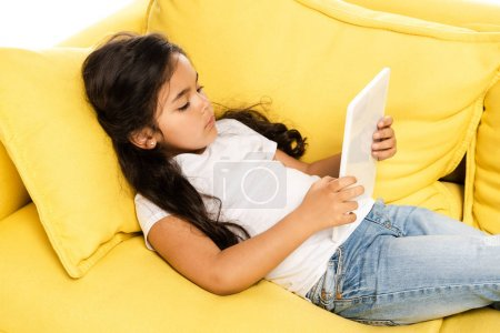 Photo for Overhead view of cute latin kid lying on yellow sofa and using digital tablet isolated on white - Royalty Free Image