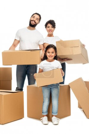 Photo for Cheerful latin parents holding boxes and standing with cute daughter isolated on white - Royalty Free Image