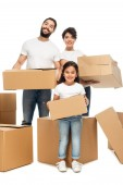 cheerful latin parents holding boxes and standing with cute daughter isolated on white
