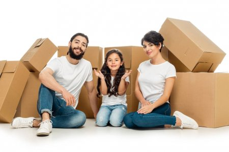 Photo for Cheerful latin parents sitting near cute daughter and carton boxes isolated on white - Royalty Free Image