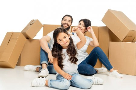 Photo for Selective focus of happy latin kid holding keys and sitting near parents and boxes isolated on white - Royalty Free Image