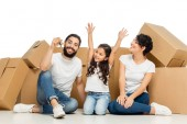 happy latin kid gesturing while looking at father holding keys and sitting near boxes isolated on white