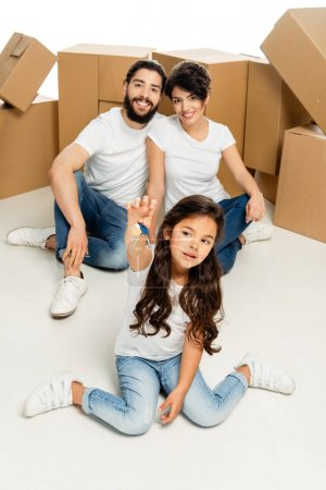 Photo for Selective focus of cute latin kid holding keys and sitting near parents and boxes isolated on white - Royalty Free Image