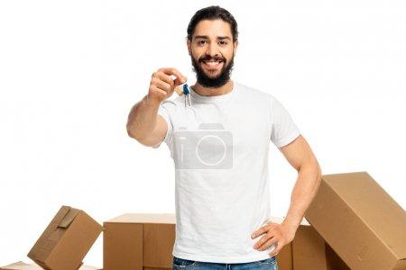 Photo pour Homme latin heureux retenant la clef et restant avec la main sur la hanche d'isolement sur le blanc - image libre de droit