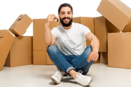 Photo for Bearded latin man holding key and sitting with crossed legs near boxes isolated on white - Royalty Free Image