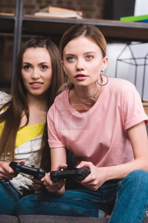 young attractive female friends  with joysticks in hands playing video game at home