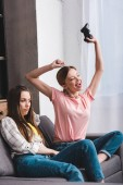 young woman with joystick celebrating victory in video game and her upset female friend sitting near on sofa
