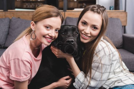 smiling young female friends embracing black retriever at home