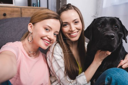 young smiling woman taking selfie with female friend and black labrador at home