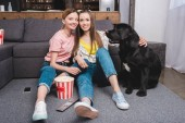 two smiling female friends with black labrador sitting on floor with remote controller, popcorn bucket and smartphone