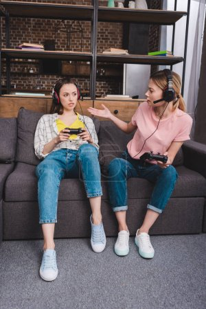 agressive young woman in headphones with joystick in hand quarreling with female friend at home