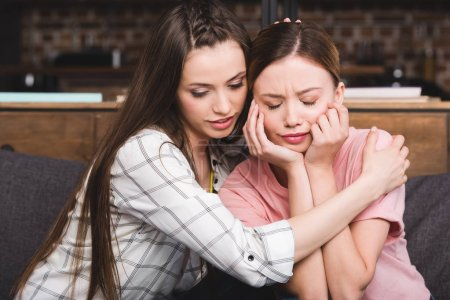young woman cheering up crying female friend at home
