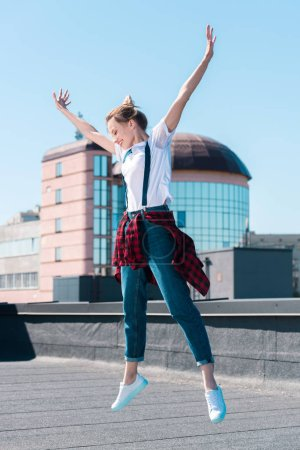 young smiling woman jumping with wide arms up at rooftop