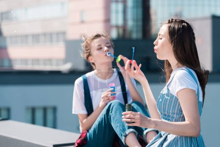 young attractive female friends using bubble blowers at rooftop