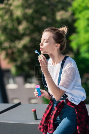 attractive young woman using bubble blower at rooftop