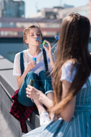 two young female friends with bubble blowers at rooftop