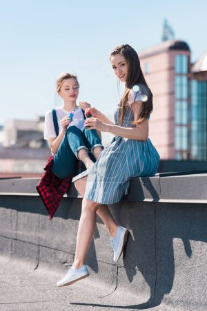 two young female friends using bubble blowers at rooftop