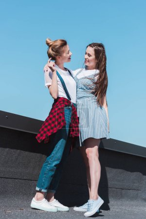 low angle view of two stylish female friends standing at rooftop