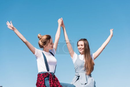 Photo for Smiling young female friends holding hands against bright blue sky - Royalty Free Image