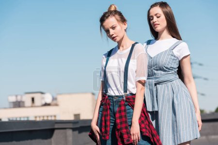 two young female friends standing at rooftop