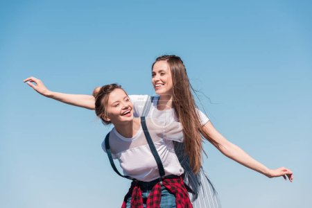 smiling young woman doing piggyback ride to female friend