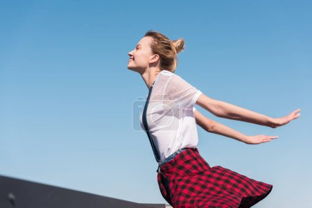 side view of happy young woman with wide arms standing against blue sky