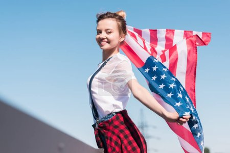 smiling young woman holding american flag against blue sky, independence day concept