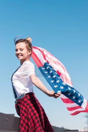 Photo pour Jeune femme tenant drapeau américain contre le ciel bleu, concept de fête de l'indépendance - image libre de droit