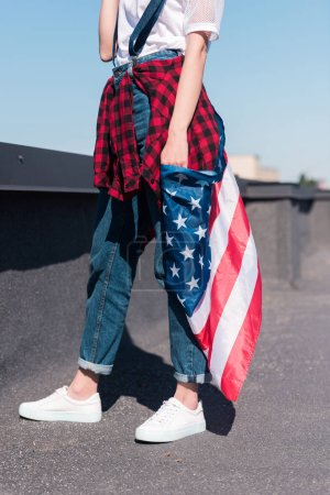 cropped shot of woman holding american flag  at rooftop, independence day concept