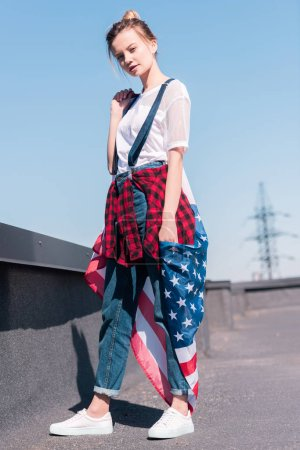 young woman holding american flag at rooftop, independence day concept