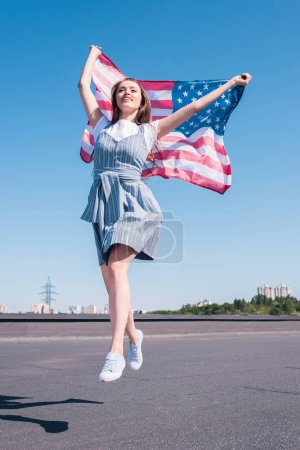 young woman jumping with united states flag at rooftop, independence day concept