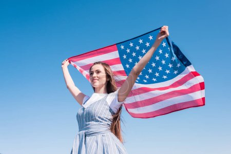 young woman holding american flag against blue sky, independence day concept