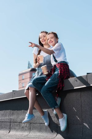 young woman pointing by finger to smiling female friend with paper cup of coffee at rooftop