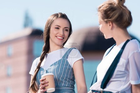 smiling young woman with paper cup of coffee talking to female friend